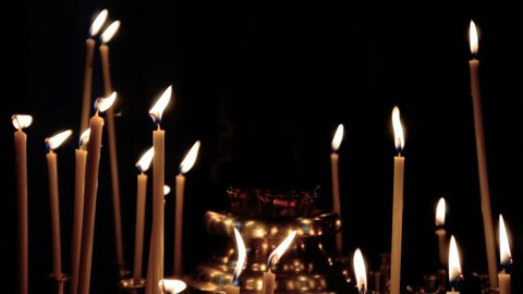 Church candles burn on a black background. Church candles and lamps
