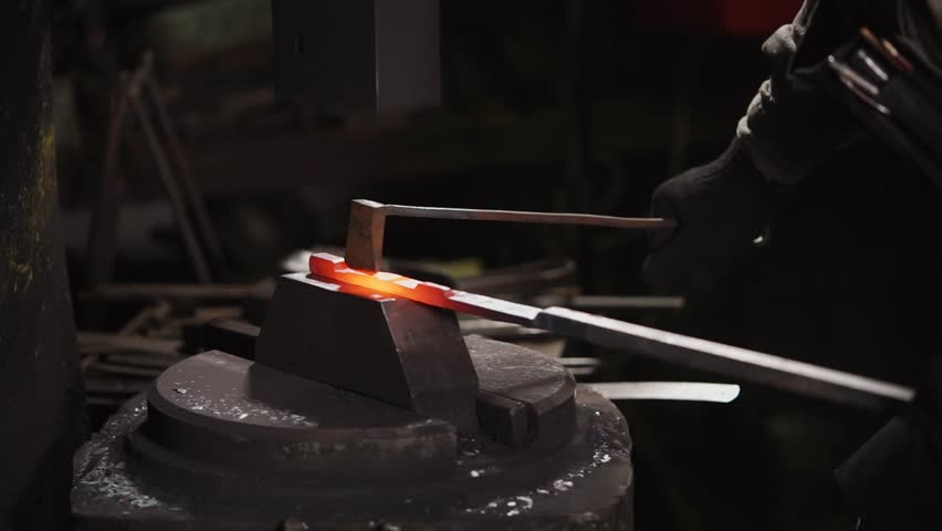 close up shot of a blacksmith's hands, a man hits the hammer with a hammer over a hot piece of steel, which will then become a horseshoe, the person is in a blacksmith shop