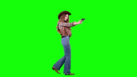 Sheriff girl holds a revolver in her hands and aiming at the villain. Green screen. Side view