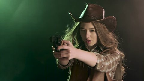 Cowgirl holds a revolver in her hands and aiming at the villain. Black smoke background. Slow motion