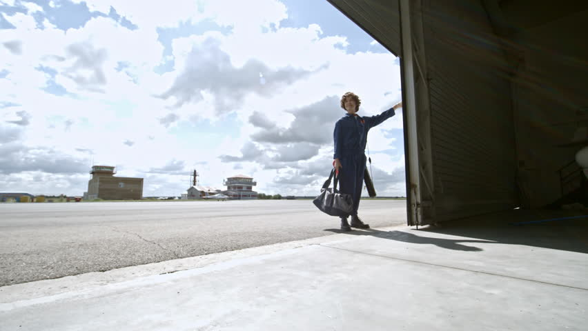 Zoom in of smiling female aircraft mechanic in uniform opening folding door and walking into hangar