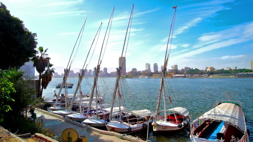 The yacht club on Corniche El Nil in Downtown, traditional feluccas are rocking on the waves with Giza cityscape on background, Cairo, Egypt.