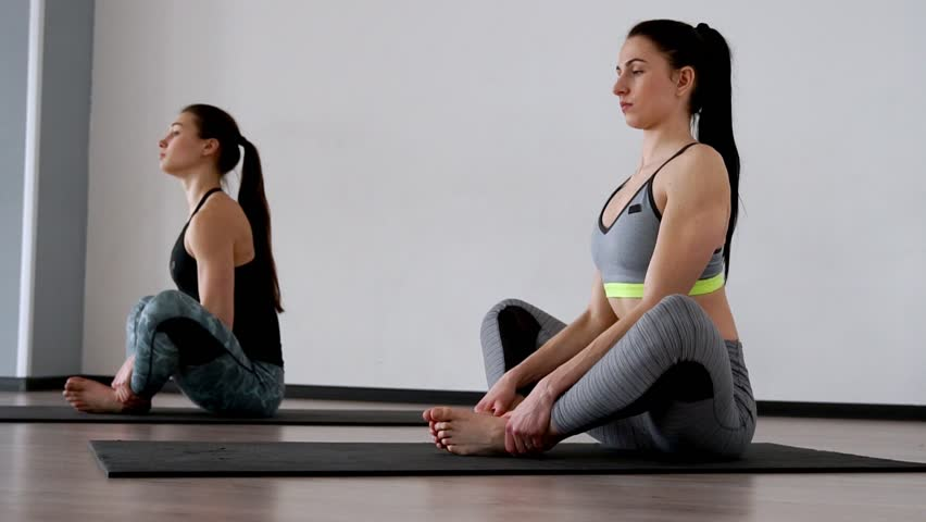 Beautiful girls perform an exercise for posture sitting in a butterfly posture. Pilates. Yoga
