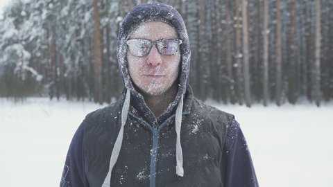 a frozen man takes off his glasses in the winter forest, after a snow storm, covered with snow