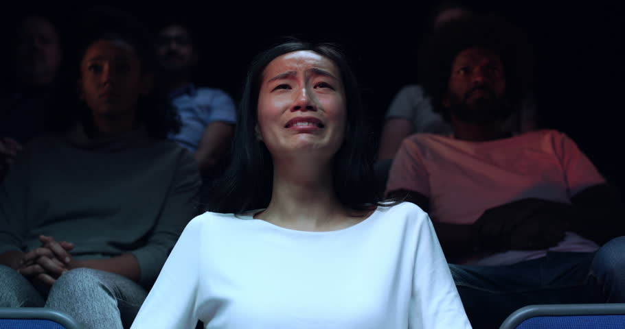 A Chinese woman at a movie theatre wipes away her tears during a sad movie.