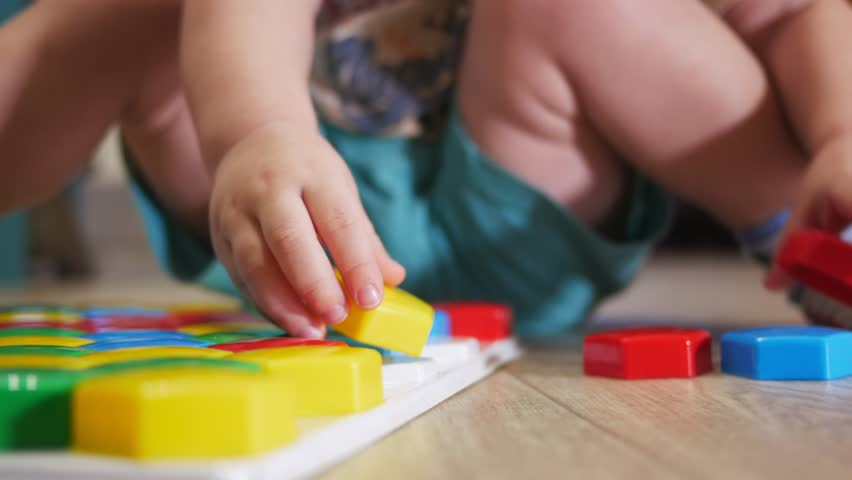 A cute child collects a picture from large multi-colored details. Playing with a puzzle