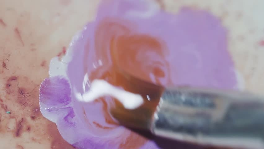 Mixing orange and purple colors with brush on dirty palette, macro close up   Shutterstock HD Video #1007282779