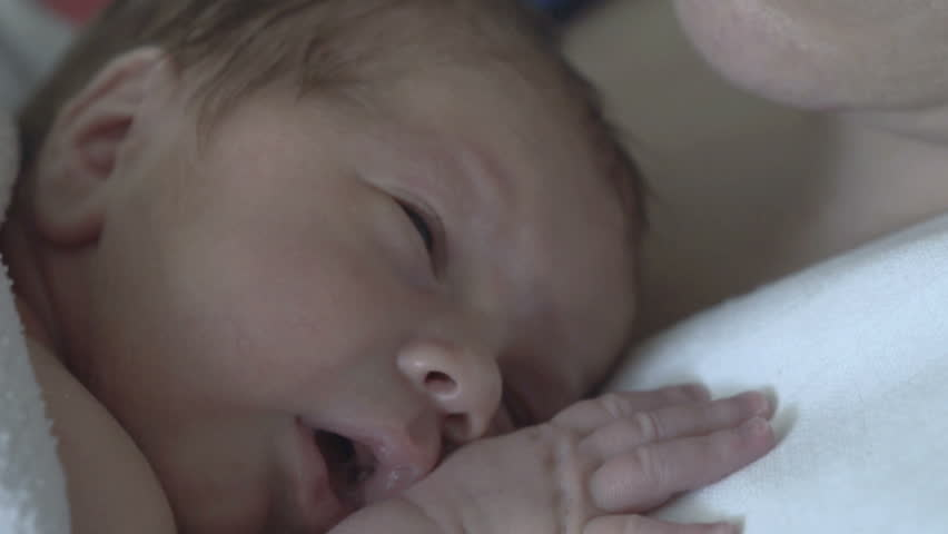 Newborn baby lying on his mother and having hiccup
