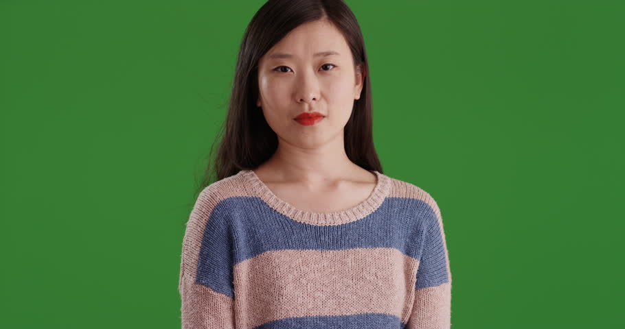 Somber asian girl looking at camera standing in front of green chromakey wall. Portrait of serious young Chinese woman on green screen. 4k
