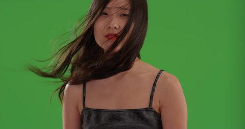 Close up of asian woman's face with hair blowing on green chroma key. Tight shot of young Chinese woman with long dark hair in the wind on greenscreen. 4k