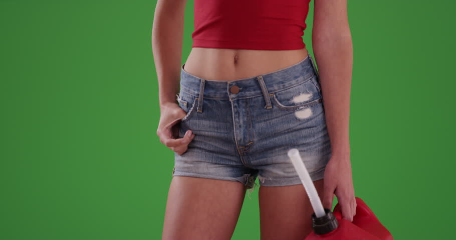 Close up of red gas can held by woman in jean shorts who ran out of fuel on her road trip on greenscreen. Stranded motorist standing with gasoline canister waiting for help. 4k on green background