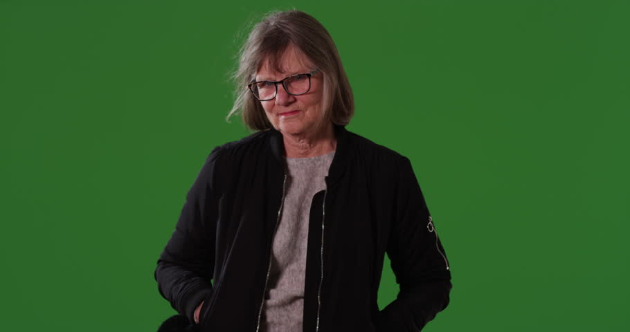 Somber senior woman with hands in pockets looking at camera on a greenscreen background. Serious caucasian woman with hair blowing in wind isolated on chroma green backdrop. 4k