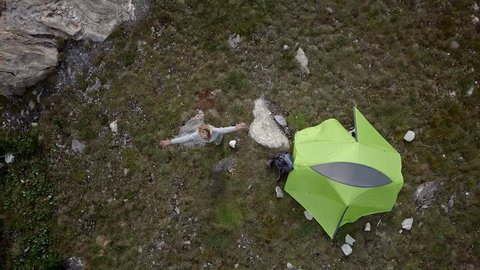 Drone shot, young woman on a hike stands by her tent near stunning mountain lake arms outstretched. Drone flies over hiker arms wide open surrounded by scenic mountain lake landscape.