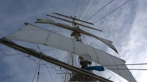 Square sails on main mast of a sailing tall ship rolling with blue sky in the background