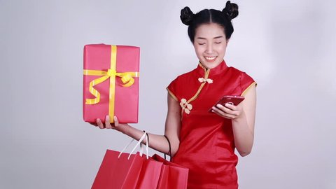 woman wear cheongsam and using mobile phone with shopping bag and gift box