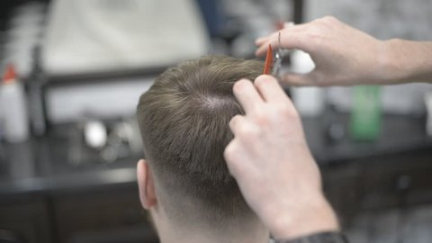 Male haircut with electric razor. Close up of hair trimmer hairstyle. Professional hairdresser cutting hair with hair clipper. Man hairdressing with electric shaver. Video without color correction.