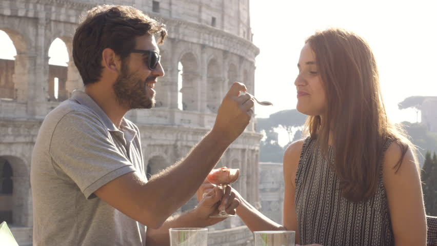Happy young couple tourists eating glass of icecream sitting at bar restaurant outside in front of colosseum in rome at sunset | Shutterstock HD Video #1007358019