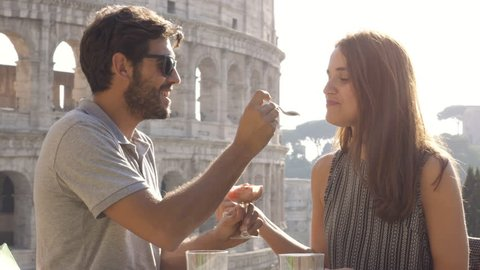 Happy young couple tourists eating glass of icecream sitting at bar restaurant outside in front of colosseum in rome at sunset
