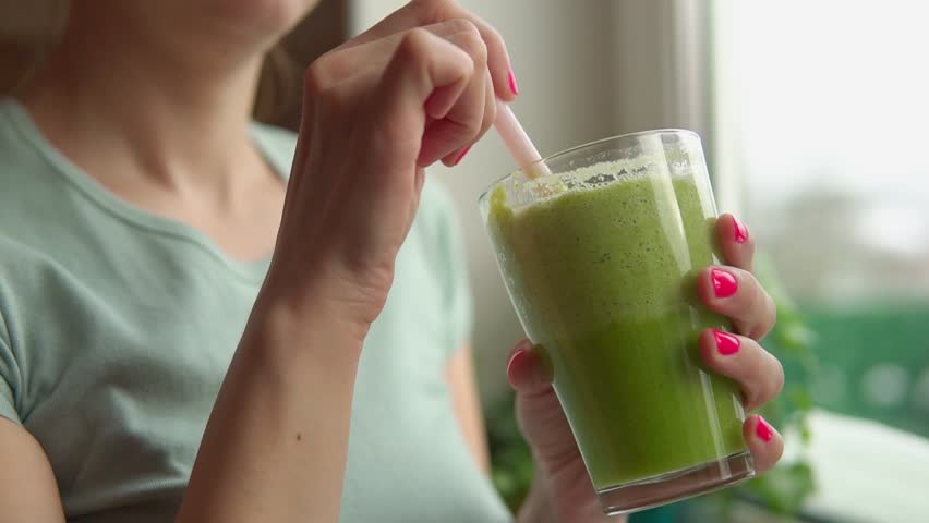 Woman is staying near window with glass of green smoothie