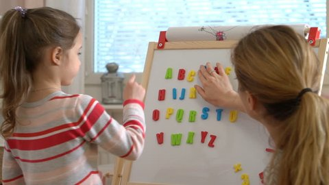 Early childhood development. Little girl are learning to write letters with special desk. Young woman teaching her child the alphabet.