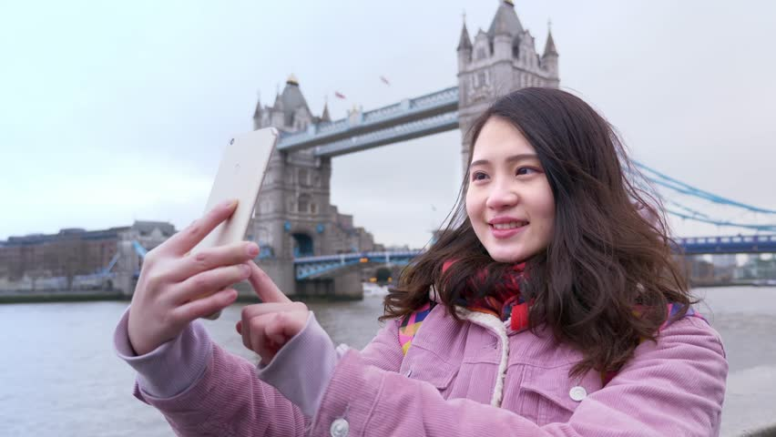Asian Young woman tourist taking photo selfie using smart phone app by  London Tower Bridge.