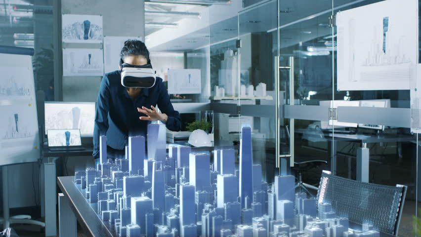 Professional Female Architect Wearing  Augmented Reality Headset Work with 3D City Model. High Tech Office Use Virtual Reality Modeling Software Application. Data Visualisation Concept.
