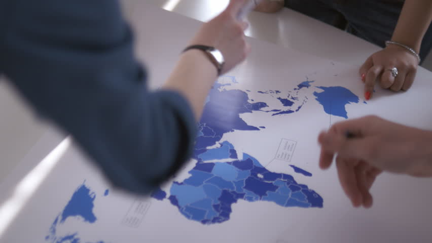 View from above of hands on the world map. Young coworkers immersed into market research analyzing the growth of import and export in a meeting.