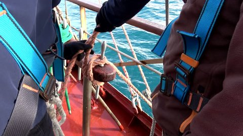 Crew of Sailing Tall Ship is preparing the sails working with lines and ropes and making knots