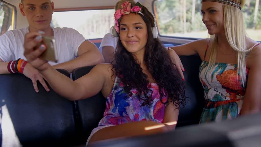 Hippie friends taking selfie on a road trip | Shutterstock HD Video #1007423509