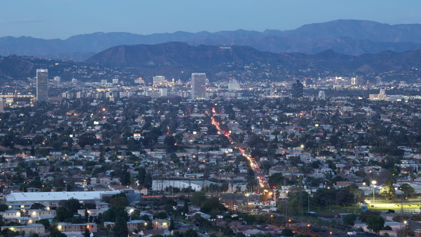 4K time lapse high angle wide shot of the Hollywood sign in Los Angeles, California and neighborhood lights after sunset transitioning to night on a partly cloudy evening
