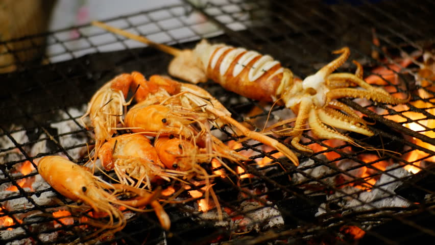 Squid Cooked on the Grill Grate in Night Food Market, Thailand Street Food. Preparation of large red Squid on a grate. Delicious Grilled Prawns or Shrimps on Barbecue Grill. Jomtien, Pattaya, Thailand