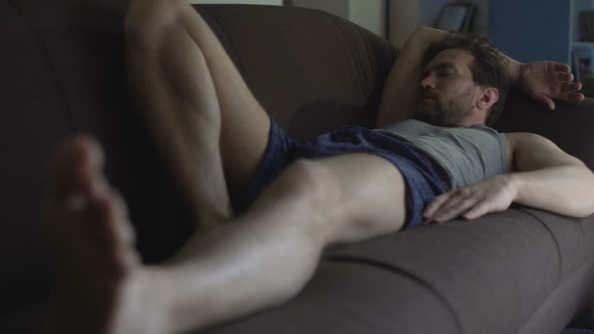 Lazy man in underwear sleeping on couch, scratching belly, apathy, problems