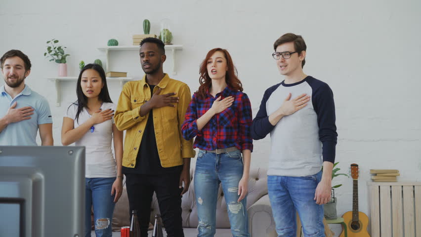Multi ethnic group of friends sport fans singing national anthem before watching sports championship on TV together at home