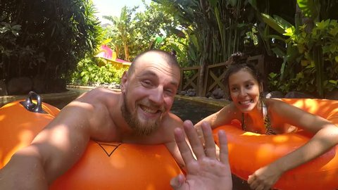 Young Mixed Race Couple Making Selfie and Waving Hands to Camera while Relaxing on Tube in Swimming Pool Lazy River Waterpark. HD.