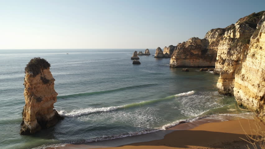 Waves breaking on sandy ocean beach Praia Dona Ana with famous beautiful coastal cliffs in Lagos, Algarve, Portugal
