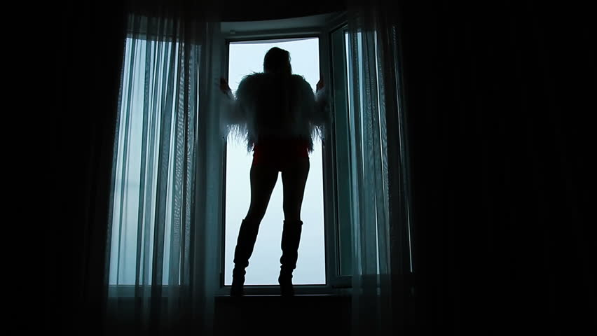 Woman in shertas and a jacket of ostrich feathers stands on the windowsill | Shutterstock HD Video #1007486029