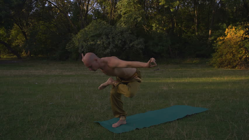 A Young Man with a Naked Tanned Torso Performing Yoga Asanas on a Glade in the Forest #1007503909