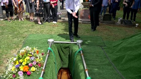 casket being lower into burial site at cemetery