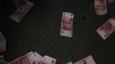 Lots of russian ruble money on green linoleum floor, rich wealth concept, small dog running around