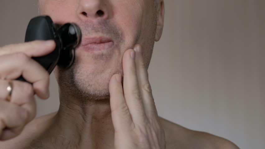 Man shaving beard with electric shaver. Closeup.
