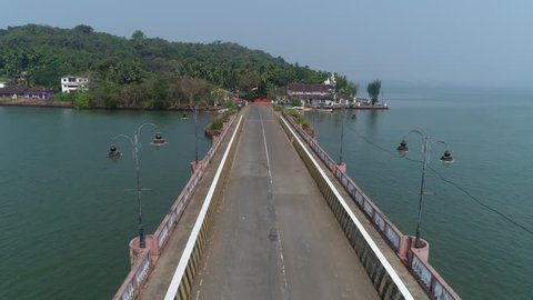 Flight over the bridge between the lampposts. Road bridge to the St. Jacinto island in Goa, India. Aerial view.