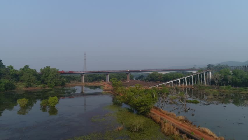 Flying over beautiful landscape a large automobile bridge over the river, on which cars ride. Beautiful reflection in the water. Aerial view. | Shutterstock HD Video #1007525980