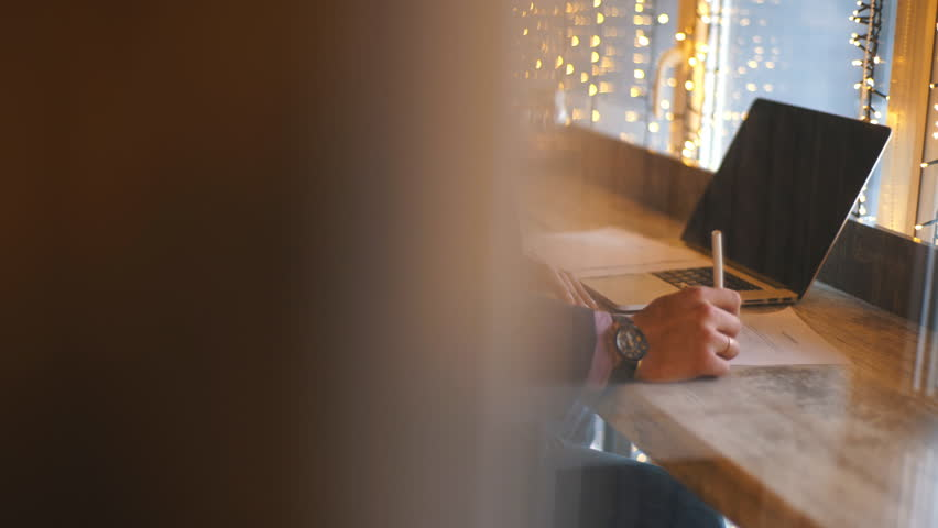 A young businessman sits in a cafe and studies the contract | Shutterstock HD Video #1007527369