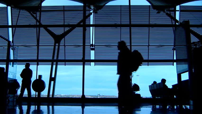Backlight of people who are walking in an airport. You can only see their silhouettes. In the background, a large window where you can see the sky.