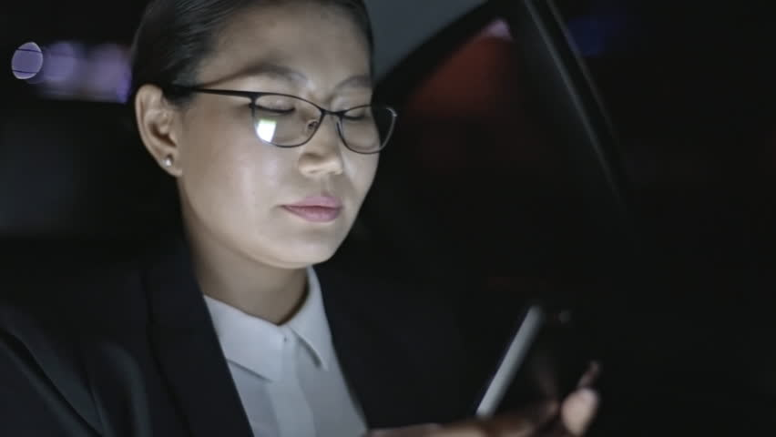Asian businesswoman in glasses typing on mobile phone and looking out window of car driving through city at night | Shutterstock HD Video #1007529649