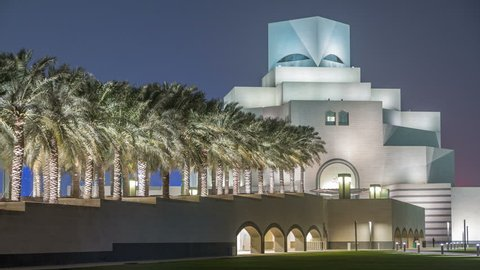 Beautiful Museum of Islamic Art illuminated at night with fountain timelapse in Doha, Qatar. Palms on the side. View from MIA park. It is one of the worlds most complete collections of Islamic