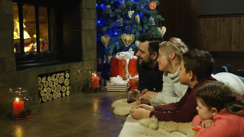 Young family relaxing on a shaggy rug in front of a burning fire and Christmas tree with burning candles as they spend time together