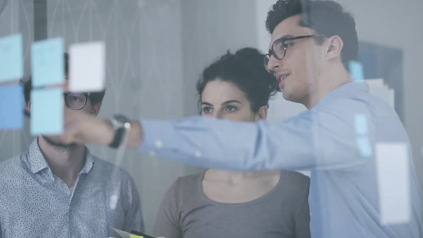 Young business team meeting in the office and discussing a project together, they are pointing at sticky notes on a glass, start up and teamwork concept | Shutterstock HD Video #1007547289