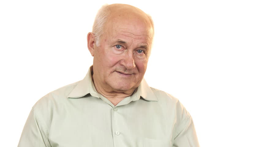 Old man looking at an alarm clock smiling to the camera