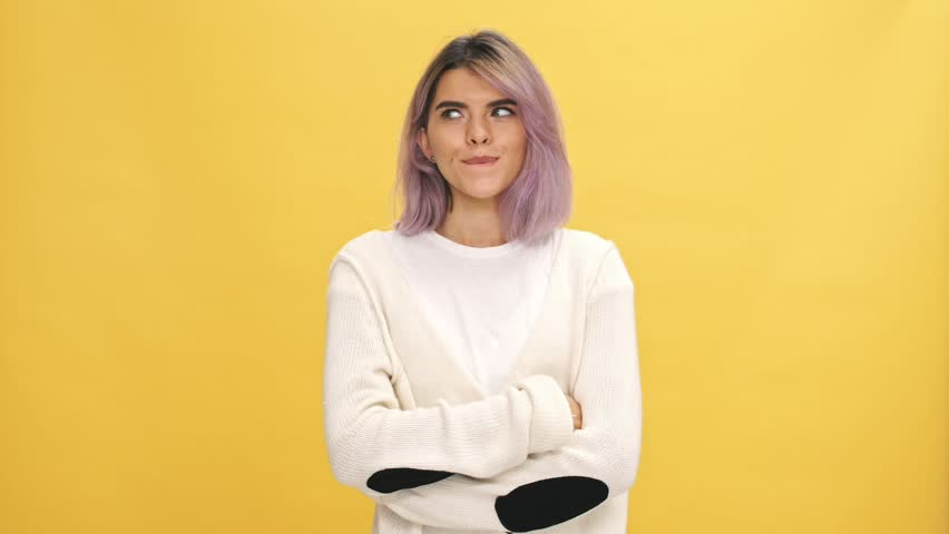 Smiling mystery woman in warm cardigan showing silence gesture over yellow background